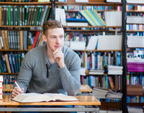Male student with open book working in a library Stock Photo