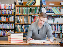 Male student with open book working in a library.  Stock Photography