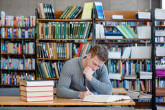 Male student with open book working in a library.  Royalty Free Stock Photography
