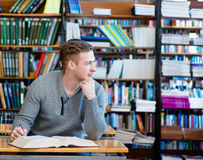 Male student with open book working in a library.  Royalty Free Stock Photos