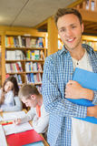 Male student with others in background at library. Portrait of a smiling male student with others in background in the college library Stock Photography