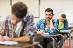 Male student with others writing notes in classroom Stock Image