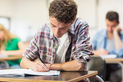 Male student with others writing notes in classroom Stock Photos