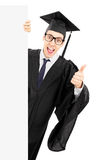 Male student peeking behind blank panel and giving thumb up. Male college graduate peeking behind blank panel and giving thumb up isolated on white background Royalty Free Stock Photos