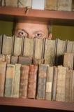 Male student peeking through library bookshelf Royalty Free Stock Photos
