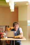 Male Student in pizzeria with Laptop. Indoor shot Royalty Free Stock Photo