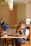Male Student in pizzeria with Laptop. Indoor shot Stock Images