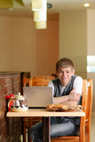 Male Student in pizzeria with Laptop. Indoor shot Stock Image