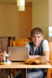 Male Student in pizzeria with Laptop. Indoor shot Stock Photography