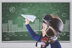 Male student playing a paper plane. Photo of a male elementary school student playing a paper plane in the class while wearing helmet and scarf Stock Photography