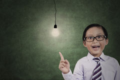 Male student pointing a bright light bulb. Image of male student is getting an idea while pointing a bright light bulb in the classroom Stock Images