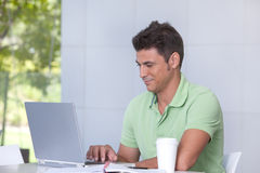 Male Student Portrait. Portrait of a male student working on laptop Royalty Free Stock Image