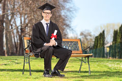 Male student posing with diploma  in park. Male student posing with diploma seated on bench in park Stock Image