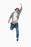 Male student posing by jumping with a raised arm. Against a white background Royalty Free Stock Photo