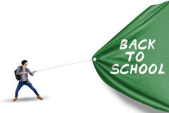 Male student pulling banner of back to school Royalty Free Stock Images