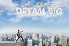 Male student pulling dream big text. Picture of a male college student standing on the roof while pulling a text of dream big from the sky Royalty Free Stock Photo
