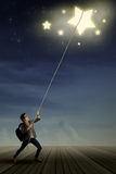Male student pulling stars. Portrait of young male student pulling stars with rope Royalty Free Stock Photography