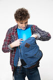 Male student pulls out of a backpack something Royalty Free Stock Images