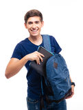 Male student putting folder in backpack. Smiling male student putting folder in backpack isolated on a white background. Looking at camera Royalty Free Stock Images
