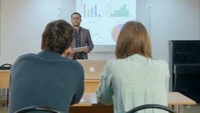 Male student raising hand and asking teacher a question sitting on table. Professional shot in 4K resolution. 075. You can use it e.g. in your commercial video Royalty Free Stock Images