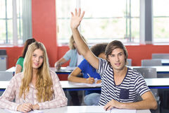 Male student raising hand in classroom. Portrait of male student raising hand in classroom Royalty Free Stock Photos