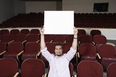 Male Student Raising Sign Board While Sitting In Classroom Royalty Free Stock Photography