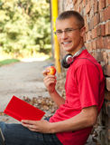 Male student reading book. Leaning on the bricks wall Stock Photos