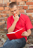 Male student reading book. Leaning on the bricks wall Royalty Free Stock Images