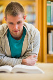 Male student reading book on the college library floor Stock Image