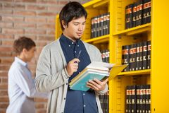 Male Student Reading Book In College Library Stock Images