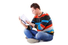 Male student reading a book isolated. Portrait of a male student sitting reading a book isolated on white Royalty Free Stock Images