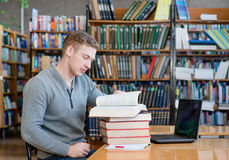 Male student reading book in library.  Stock Photography