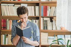 Male student reading book in library. Background Stock Photography
