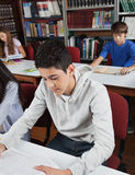 Male Student Reading Book In Library. Male high school student reading book at table with classmates in library Royalty Free Stock Photos