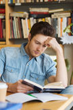 Male student reading book in library Royalty Free Stock Image