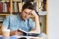 Male student reading book in library. People, knowledge, education and school concept - male student reading book in library Stock Photography