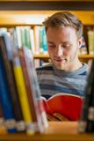 Male student reading a book in the library. Young male student reading a book amid bookshelves in the college library Royalty Free Stock Photo