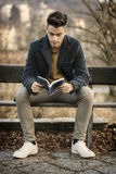 Male student reading book outdoor. Handsome young man reads a book sitting outside on a bench in city park Royalty Free Stock Image