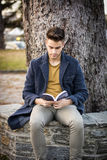 Male student reading book outdoor. Handsome young man reads a book sitting outside on a bench in city park Stock Images