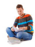 Male student reading a book preparing for exam iso. Full length male student sitting on floor reading a book preparing for exam isolated on white background Stock Image