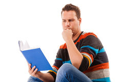 Male student reading a book preparing for exam isolated. Portrait of a male student sitting reading a book preparing for exam isolated on white Stock Photography