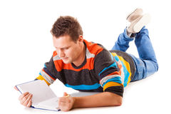 Male student reading a book preparing for exam isolated. Full length male student lying on floor reading a book preparing for exam isolated on white background Stock Photography