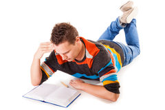 Male student reading a book preparing for exam isolated. Full length male student lying on floor reading a book preparing for exam isolated on white background Royalty Free Stock Photos