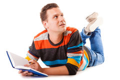 Male student reading a book preparing for exam isolated. Full length male student lying on floor reading a book preparing for exam isolated on white background Royalty Free Stock Images