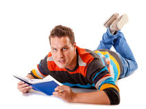 Male student reading a book preparing for exam isolated. Full length male student lying on floor reading a book preparing for exam isolated on white background Stock Images