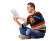 Male student reading a book preparing for exam isolated. Full length male student sitting on floor reading a book preparing for exam isolated on white background Stock Photos