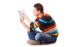 Male student reading a book preparing for exam isolated. Full length male student sitting on floor reading a book preparing for exam isolated on white background Stock Image