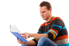 Male student reading a book preparing for exam isolated. Portrait of a male student sitting reading a book preparing for exam isolated on white Royalty Free Stock Images