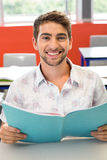 Male student reading notes in classroom. Portrait of smiling male student reading notes in classroom Stock Image