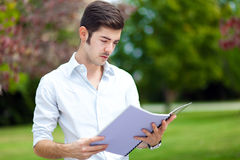 Male student reading outdoor. Male student reading at the park Stock Photography